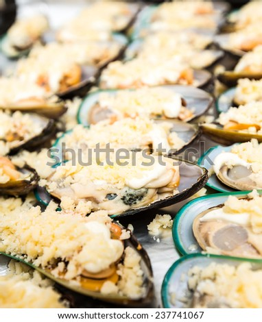 clams in shells lying in a row with spices - stock photo