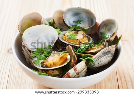 Clams steamed in white bowl on wooden table - stock photo