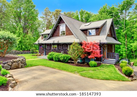 Clapboard siding brown house with green lawn and amazing blooming trees. View from the driveway - stock photo