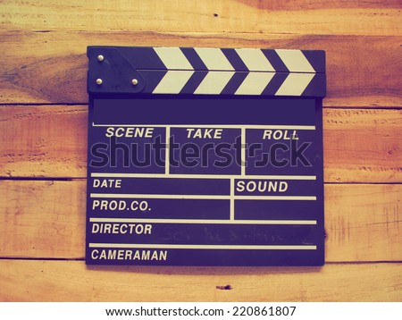 clapper board on wood background vintage color tone - stock photo