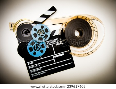 Clapper board with 8mm and 35mm film reels in white background and vintage color effect - stock photo