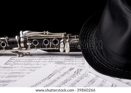 Clarinet, under a hat -  isolated over sheet music - stock photo