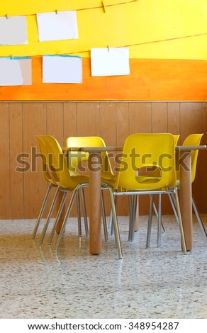 class of a kindergarten with tables and yellow chairs - stock photo