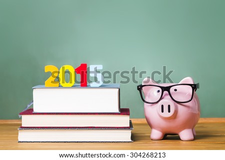Class of 2015 theme with textbooks and piggy bank with glasses on green chalkboard background - stock photo