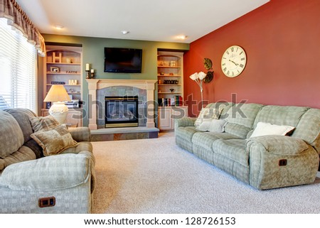 Classic American cozy living room interior with fireplace and red wall. - stock photo
