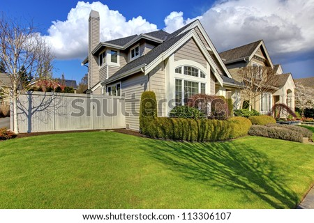 Classic American house with fence and green grass during spring. - stock photo