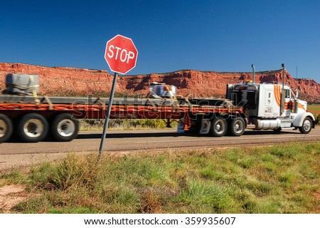 Classic American truck passing by the stop sign somewhere in Utah, USA. - stock photo