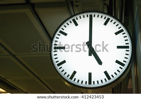Classic analog clock pointing at 5 o'clock with dark background - stock photo