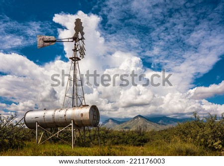 Classic antique Windmill with beautiful clouds as backdrop.  - stock photo