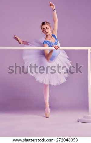 classic ballet dancer in white tutu posing on one leg at ballet barre on a lilac background - stock photo