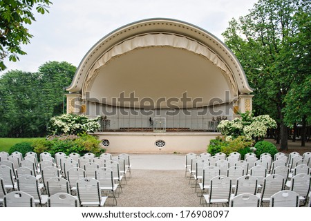 Classic band shell amphitheater with lots of white luxury seats - all surrounded by green trees and white seats - stock photo