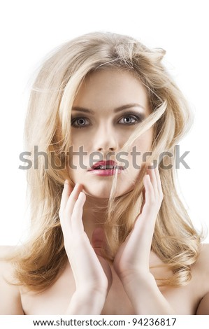 classic beauty portrait of young sexy girl with hairstyle and flying hair from wind, she is in front of the camera, looks in to the lens and has both hands near the face - stock photo