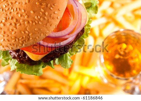 classic beef cheeseburger with potato fries and beer on background, shallow dof - stock photo