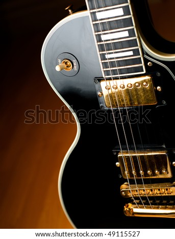 Classic black rock and roll or jazz guitar in soft spotlight. Stage or studio concept ready to perform. - stock photo