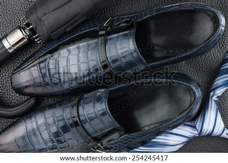 Classic blue men's shoes, tie, umbrella on the black leather, can be used as background