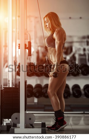 Classic bodybuilding. Muscular blonde woman doing exercises in the gym.  Fitness woman in the gym. Bodybuilder woman in the gym. Fitness woman with dumbbell. Fit woman - stock photo