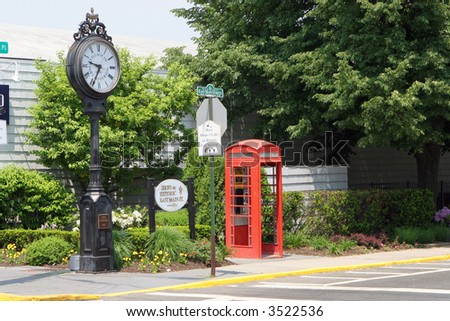 Classic british phone booth next to street clock - stock photo
