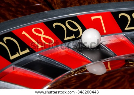 Classic casino roulette wheel with black sector twenty-nine 29 and white ball and sectors 22, 18, 7, 28 - stock photo