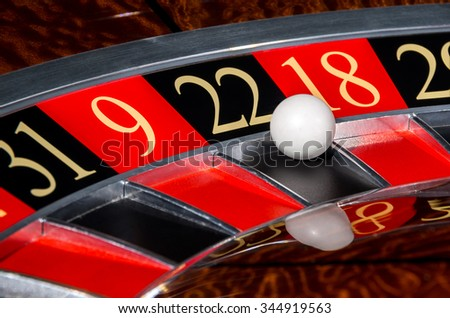 Classic casino roulette wheel with black sector twenty-two 22 and white ball and sectors 31, 9, 18, 29 - stock photo