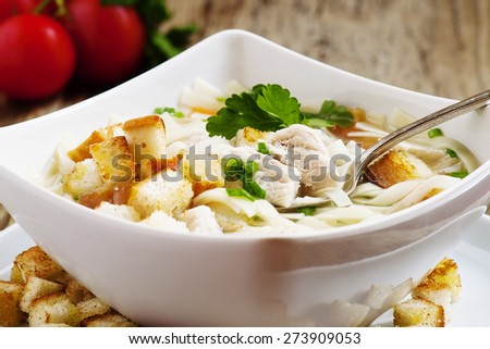 classic chicken noodle soup with crackers, selective focus - stock photo