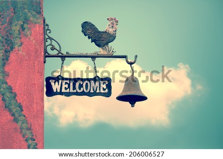 Classic Door Bell with silhouette  of  chicken, vintage welcome label  on blue sky with cloud - stock photo