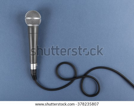 Classic dynamic microphone on a blue  background - stock photo