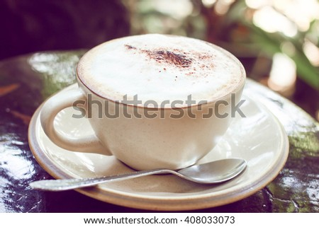 Classic foamy cappuccino in on a dark grained wood table. - stock photo