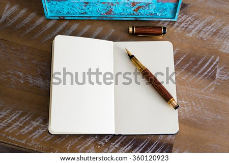 Classic fountain pen and open notebook on wooden table, with turquoise photo frame in background, copy space available - stock photo