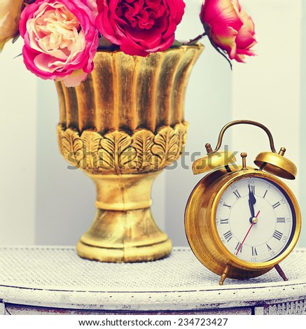 classic gold clock  watch in bright colorful retro interior behind red flowers - stock photo