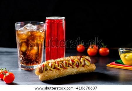 Classic hot dog on a wooden table and a glass of drink - stock photo