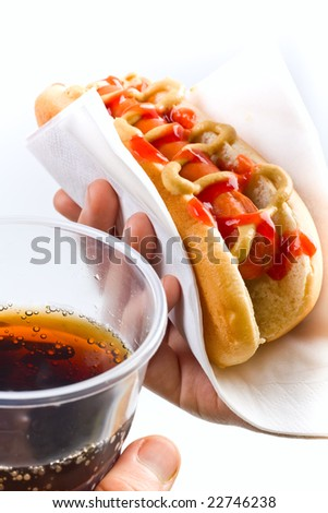 classic hot dog with mustard and ketchup and cola in hands - stock photo
