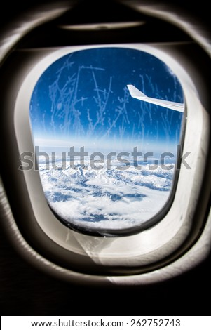 Classic image through aircraft window onto jet engine. Frost on the glass window. Focus on the wing of the aircraft. - stock photo
