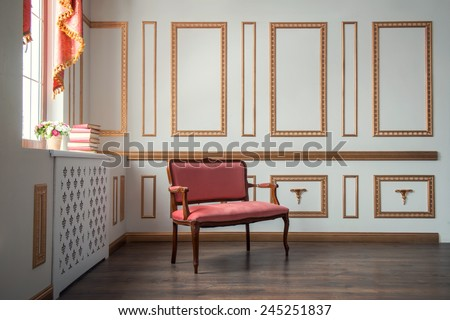 Classic interior design. Elegant interior in red and golden colors with a vintage couch standing against the wall decorated with golden moldings in day light - stock photo