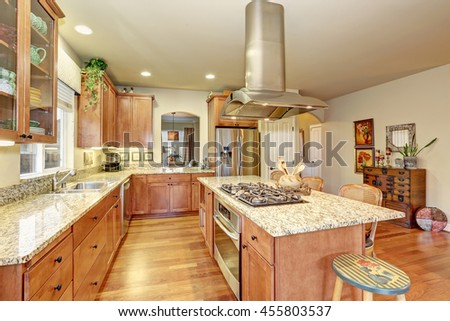 Classic large wood kitchen interior with hardwood floor, breakfast table. - stock photo