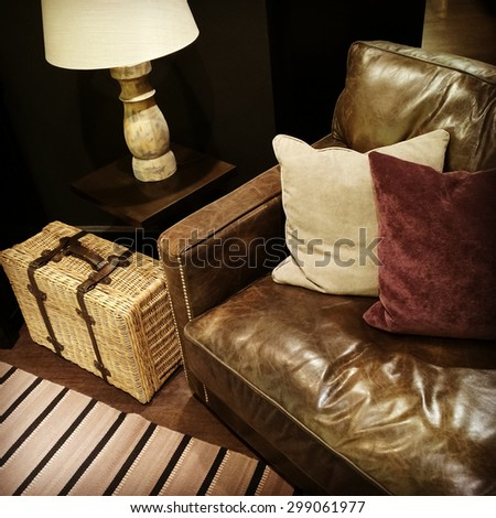 Classic leather sofa with cushions, lamp and rattan suitcase. - stock photo