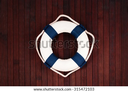 Classic lifebuoy on a wooden planks background. - stock photo