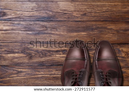 Classic male brown leather shoes on wooden background - stock photo
