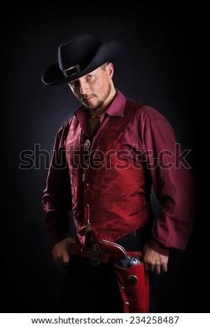 classic male cowboy with handgun closeup portrait - stock photo
