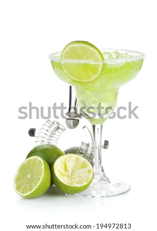 Classic margarita cocktail with salty rim, limes and drink utensils. Isolated on white background - stock photo