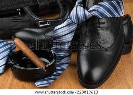 Classic men's shoes, tie, umbrella, cigar, ashtray  and bag on the wooden floor, can be used as background - stock photo