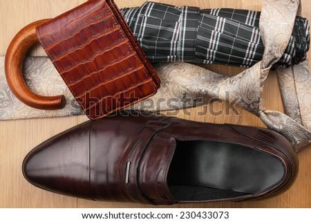 Classic men's shoes, tie, wallet, umbrella on the wooden floor - stock photo