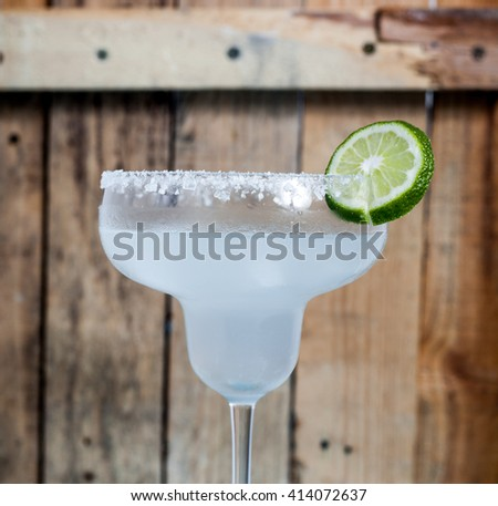 Classic Mexican Cocktail - Margarita in glass with cocktail tubes. Ingredients of cocktail - lime juice, ice, tequila, salt and orange liqueur. Rustic wood bacgkround.  - stock photo