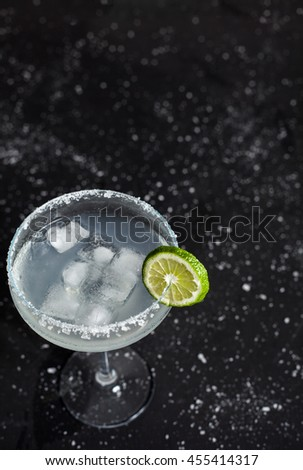 Classic mexican margarita cocktail on black background. Margarita glass full of ice, salt and lime on side. Black background with whites sea salt spots. - stock photo