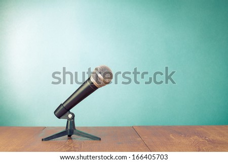 Classic microphone on table front aquamarine wall background - stock photo