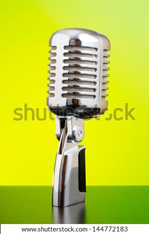 Classic microphone on yellow and green background - stock photo