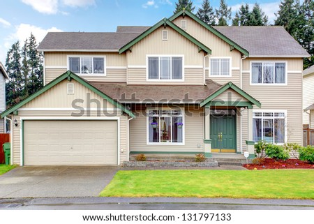 Classic new Northwest American large house exterior with beige and green. - stock photo