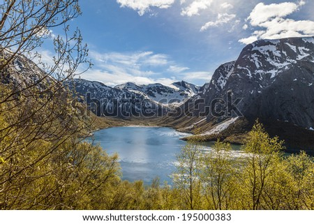 Classic Norwegian fjord with ocean surrounded by tall mountains. - stock photo