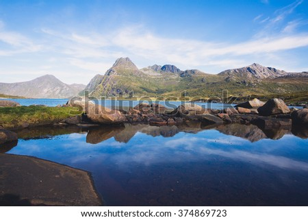 Classic norwegian scandinavian summer landscape with mountains, fjord, lake and a church, with a blue sky, Norway, Lofoten Islands - stock photo