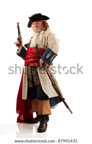 Classic old bearded pirate captain in authentic looking costume standing defiantly with his legs apart and gun upraised. Vertical format with copy space. - stock photo
