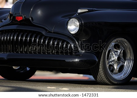 Classic old car showing only the front fender, headlight, tire and grill. - stock photo